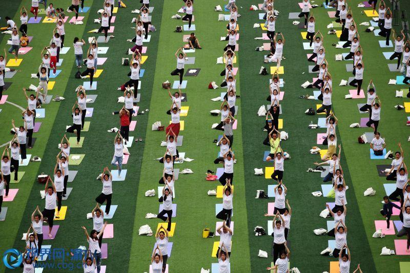 6月21日,在重庆市黔江区体育场,瑜伽爱好者在练瑜伽。当天是国际瑜伽日和二十四节气的夏至,500多名瑜伽爱好者在黔江区体育场齐练瑜伽,迎接夏至的到来。(摄影:杨敏)