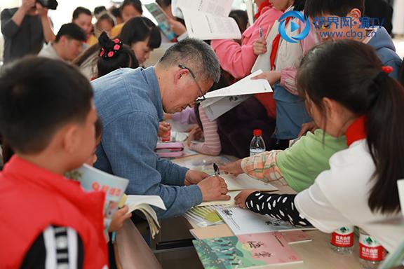 图3孩子们让作家们签名。杨雪摄.JPG